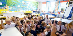 Children in classroom sitting on floor with their hands up