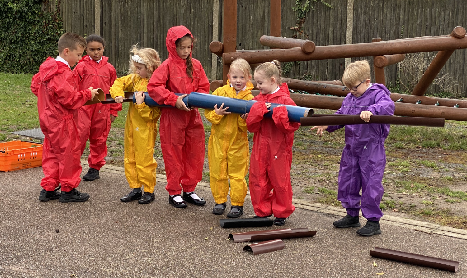 A group of students are shown working together to connect a large pipe.